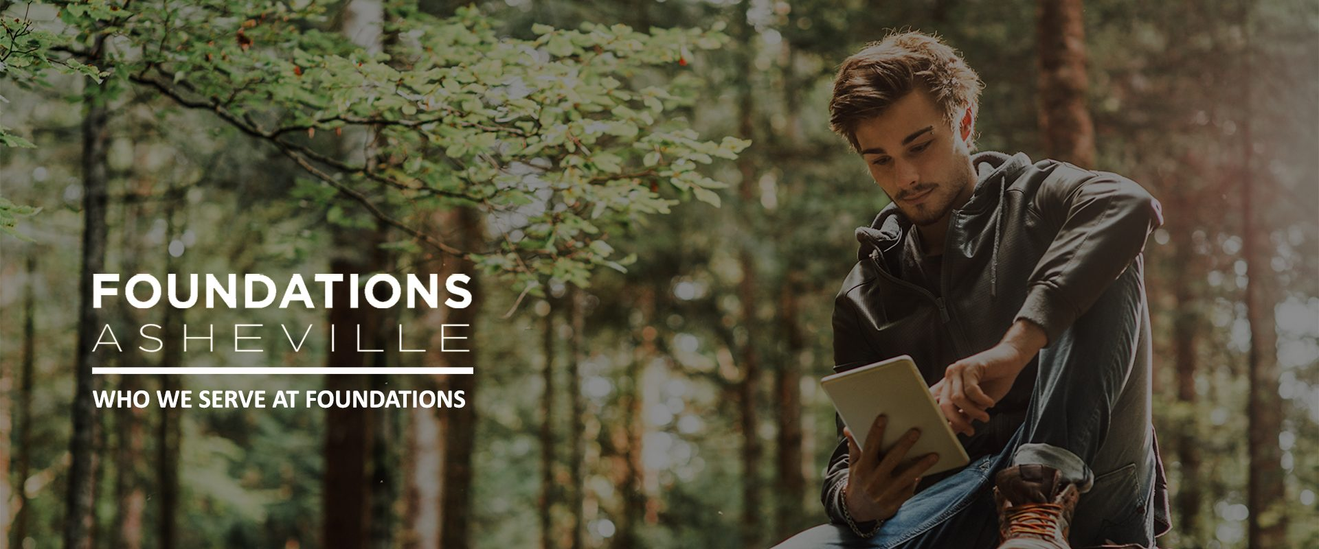 Young handsome man sitting in the woods and using a digital touch screen tablet, wi-fi connection and freedom concept